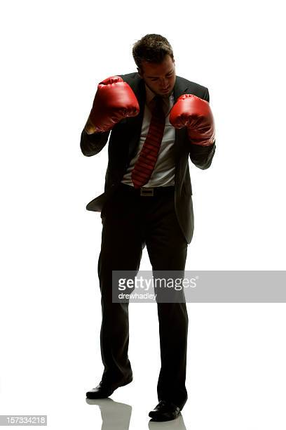 Shadow Boxing Businessman in suit with red boxing gloves.
