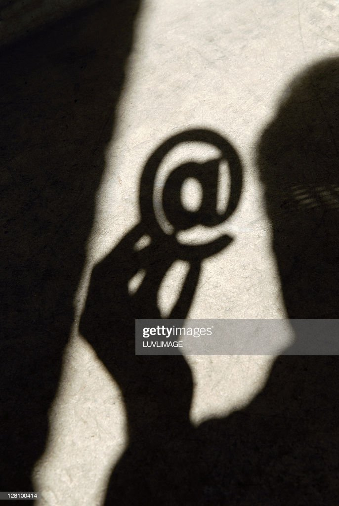 Shadow casted of man holding at AT sign