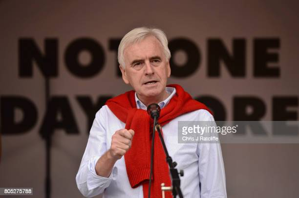 Shadow Chancellor of the Exchequer John McDonnell speaks to demonstrators during the 'Not One Day More' march at Parliament Square on July 1 2017 in...