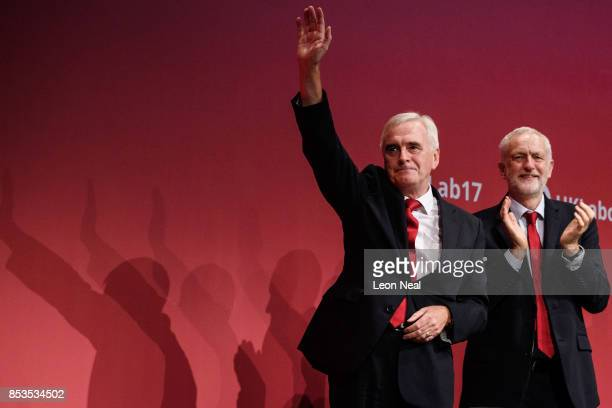 Shadow Chancellor of the Exchequer John McDonnell stands with party leader Jeremy Corbyn as he accepts applause following his address to delegates in...