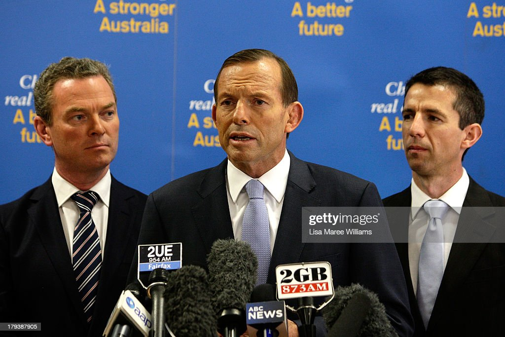 Shadow Education minister, Christopher Pyne (L) and Simon Birmingham MP (R) look at Australian Opposition Leader, <a gi-track='captionPersonalityLinkClicked' href=/galleries/search?phrase=Tony+Abbott&family=editorial&specificpeople=220956 ng-click='$event.stopPropagation()'>Tony Abbott</a> as he speaks to workers and the media at Penrice Soda Holdings on September 3, 2013 in Adelaide, Australia. In the 2010 election the Australian Labor Party recorded its highest two-party-preferred vote since 1969 in South Australia, but if nationwide polling proves accurate the Liberal-National Party coalition believe they can gain seats in the state.