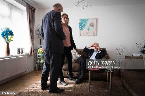 Shadow housing minister John Healey waits as Labour leader Jeremy Corbyn takes a phone call in the home of Don and Marilyn Bashford who they visited...