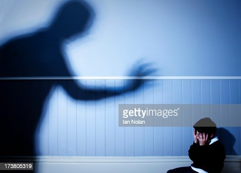 Shadow looming over frightened boy