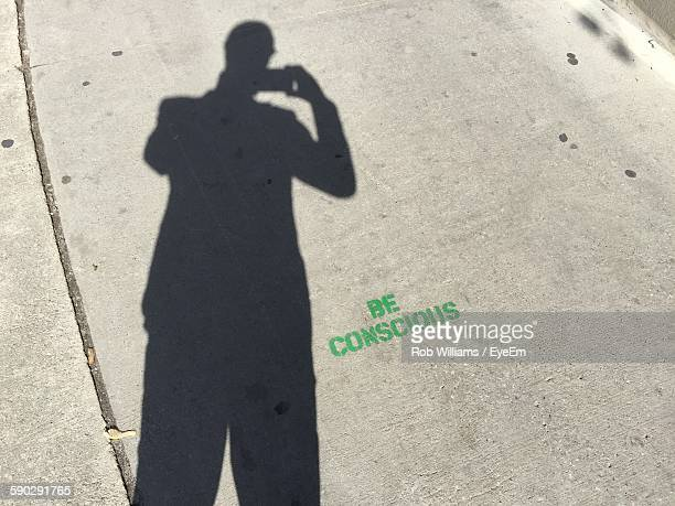 Shadow Man Photographing Through Mobile Phone On Street