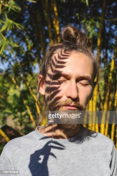 Shadow of a fern leaf on a mans face