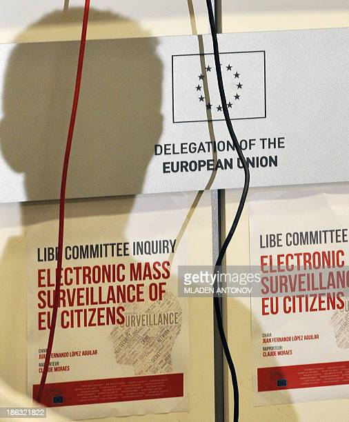 A shadow of a journalist is casted on posters announcing the visit of a European Parliament delegation visit to the US during a press conference at...