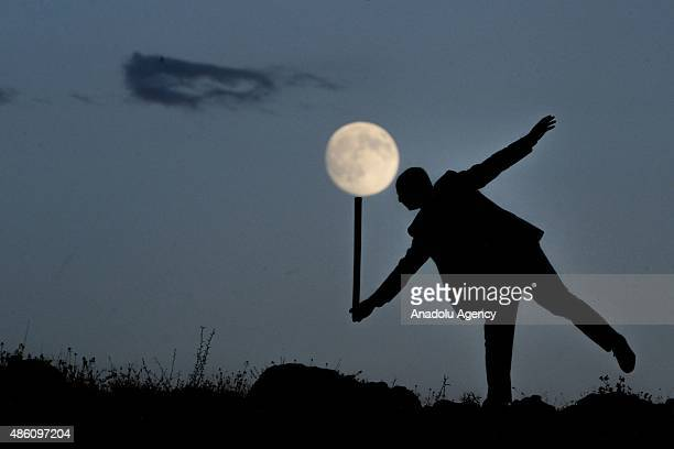 Shadow of a man holding a stick is seen in front of the supermoon in Turkey's Van on August 31 2015 The sight of a perigee moon happens when the moon...