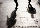 Shadow of two person on pattered sidewalk in black and white