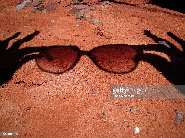 Shadow of a person holding sunglasses