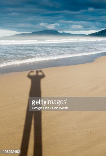 shadow of a person with arms raised on the sand of los lances beach : Stock Photo
