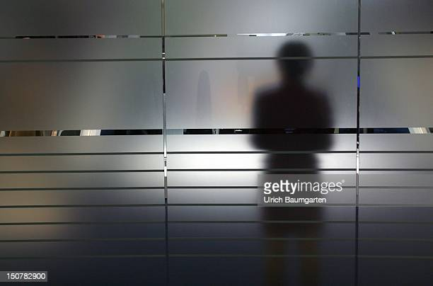 Shadow of a woman on a frosted glass pane Symbolic photo to the topics anonymity fear uncertainty unsteadiness personal secrets etc