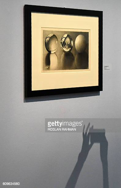 A shadow of a woman's hands emerges as she takes a picture at the art exhibition 'Journey to Infinity Escher's World of Wonder' which showcases the...