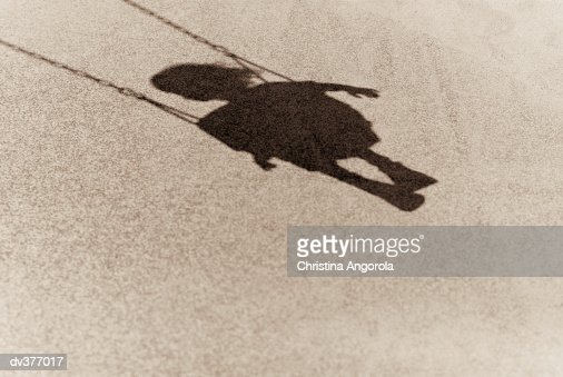 Shadow of a young child on swing : Stock Photo