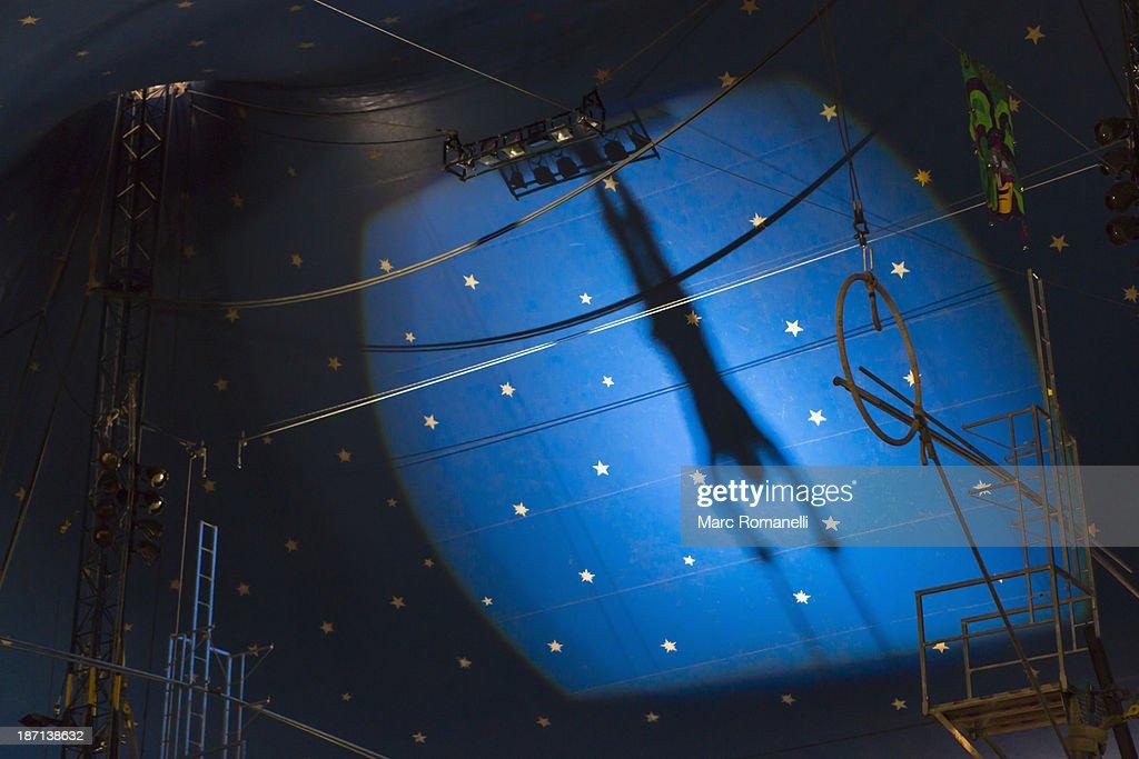 Shadow of acrobat in spotlight on wall