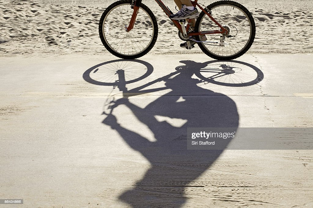 Shadow of bike rider on the beach boardwalk : Stock Photo