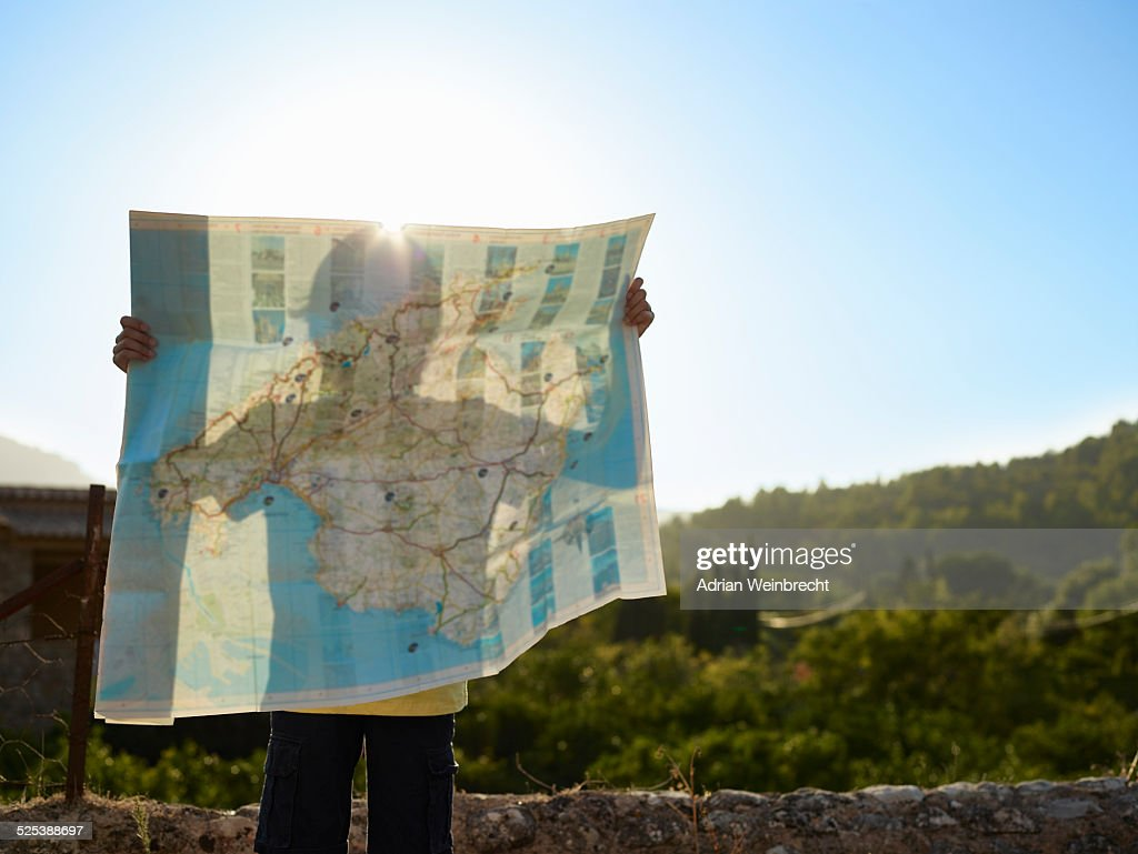 Shadow of boy holding up a map, Majorca, Spain