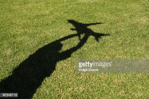 Shadow of boy holding up toy aeroplane : Stock Photo
