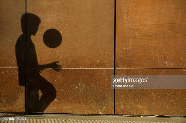 Shadow of boy (10-11) playing football in street