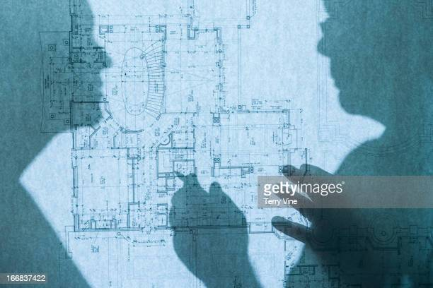 Shadow of business people on blueprints