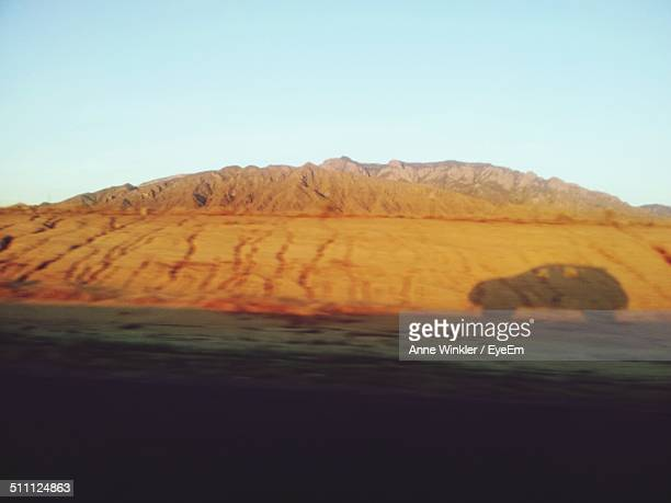 Shadow of car on desert land