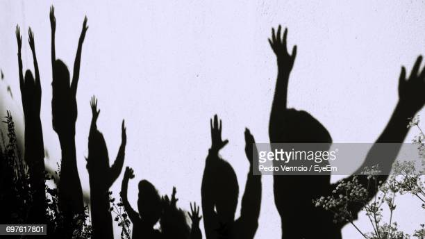 Shadow Of Children With Hands Raised On Wall