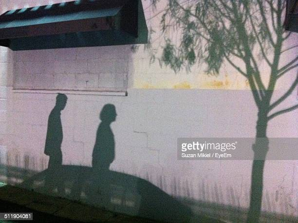 Shadow of couple and car on wall