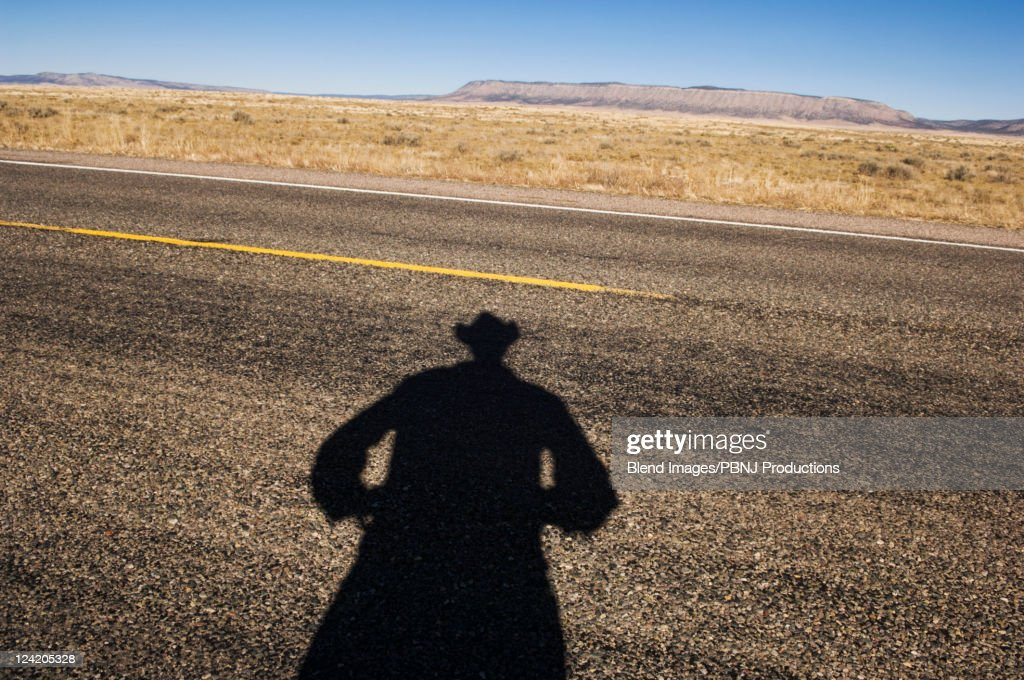 Shadow of cowboy on remote highway : Stock Photo