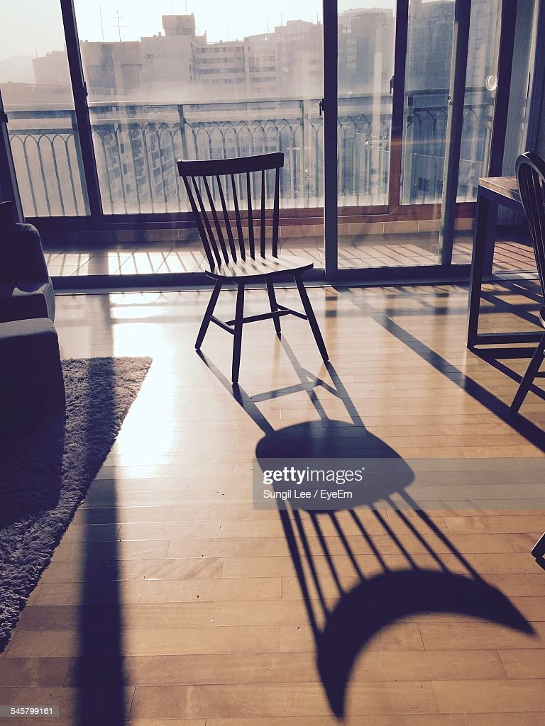 Empty chair in room - Shadow Of Empty Chair On Floor At Home