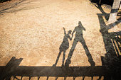 Shadow of father and daughter playing in the park