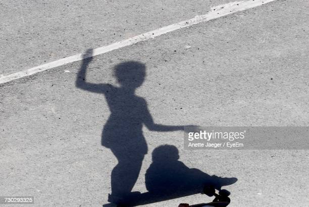 Shadow Of Girl With Child On Skateboarding At Street During Sunny Day