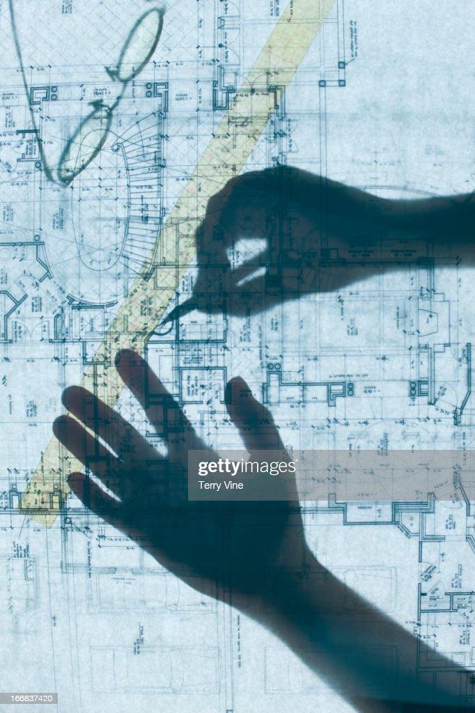 Shadow of hands on blueprints