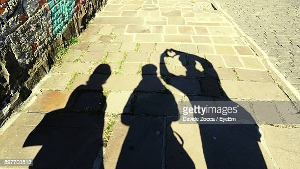 Shadow Of Man And Woman On Footpath