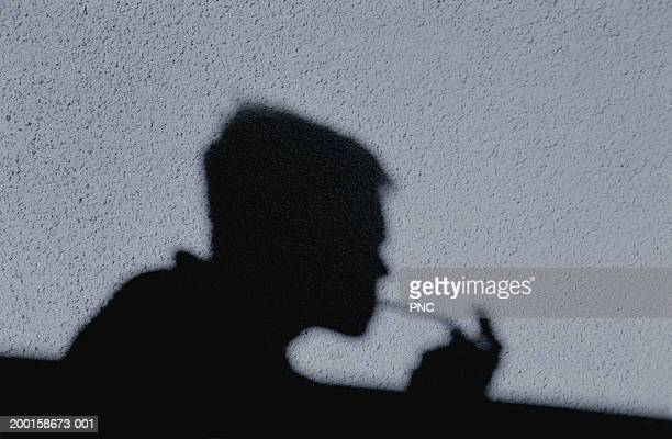 Shadow of man smoking crack cast on wall, side view