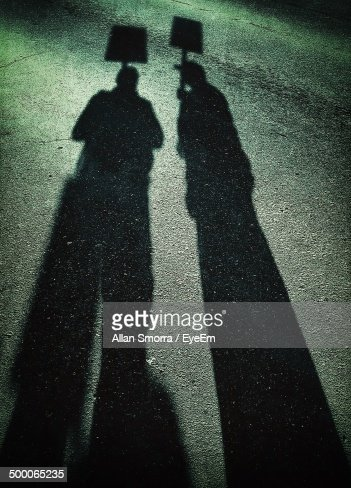 Shadow of people holding up placards