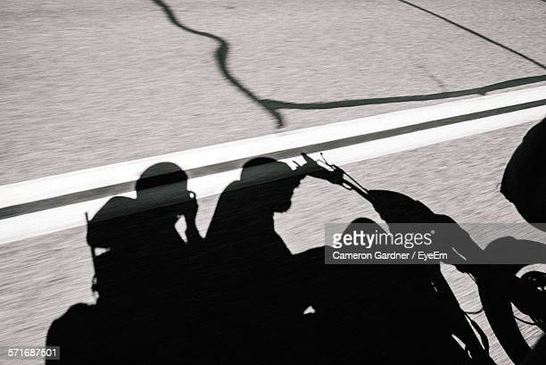 Shadow Of People On Motorbike On Road