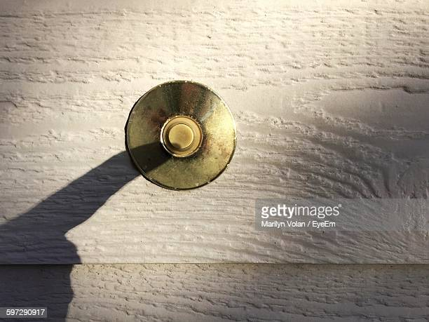 Shadow Of Person Ringing Doorbell On Wall