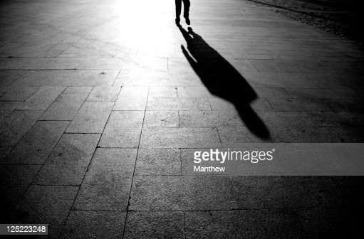 Shadow Of Person Walking On Street Stock Photo | Getty Images