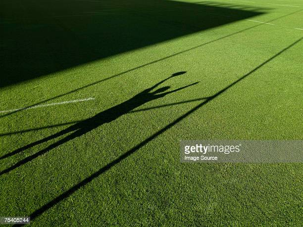 Shadow of rugby player and rugby post