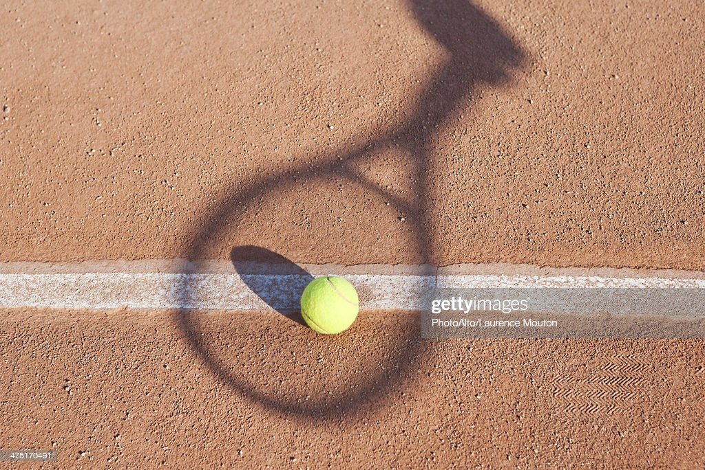 Shadow of tennis racket over tennis ball : Photo