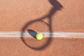 Shadow of tennis racket over tennis ball