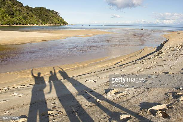Shadow of three people on the beach at Bark Bay, Abel Tasman National Park