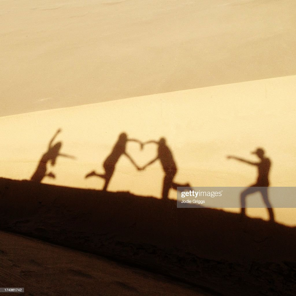 Shadow on sand dune of people making love heart : Stock Photo