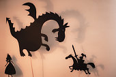 Black silhouettes of Dragon, Princess and Knight with bright glowing screen of shadow theatre in the background.