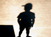 Shadow silhouette of one boy with a cap standing alone