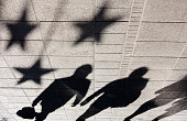Shadow silhouette of people under star shaped ornaments on city street in black and white