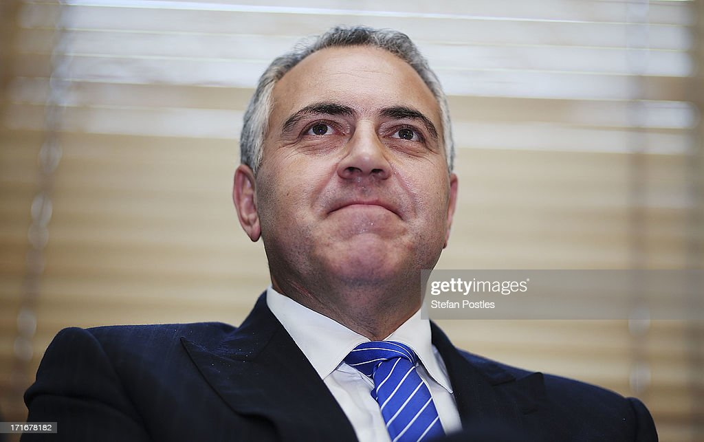 Shadow Treasurer Joe Hockey listens to Opposition Leader Tony Abbott speak to Coalition MPs in the party room on June 28, 2013 in Canberra, Australia. Abbott questioned the credibility of Kevin Rudd's new front bench during his address to Coalition MPs, one day after Kevin Rudd was sworn in as Prime Minister following a Labor party leadership ballot.