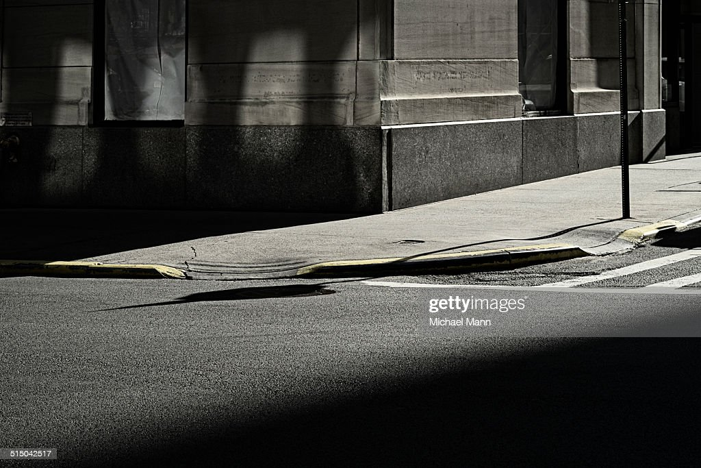 Shadowed road, pavement and building corner