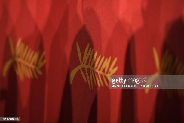 Shadows are cast onto the Palme d'Or logo on May 13 2016 during a press conference for the film 'I Daniel Blake' at the 69th Cannes Film Festival in...