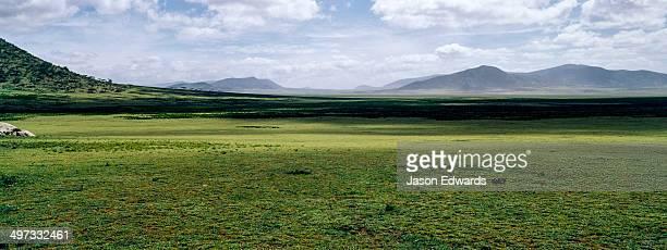 Shadows fall across a vast savannah plain to distant mountains on the horizon.