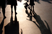 Blurry shadows of a family with little girl pushing a small bike on summer promenade
